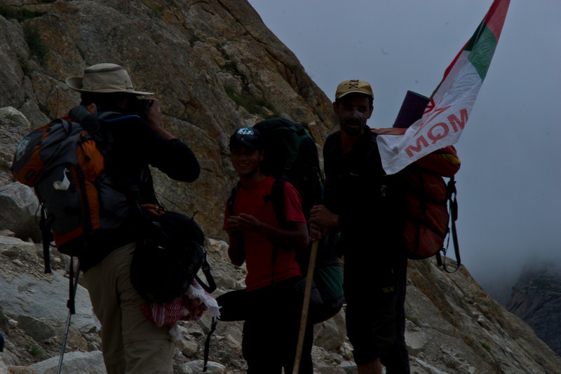 Asif poses with a climber carrying an MQM flag on his way back down.