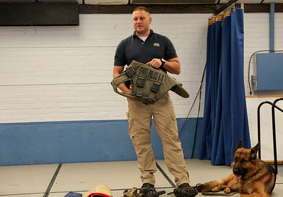 Trooper Greg Fascendini and Ale show the K9 vest purchased with funds donated by the Kids Care Club at Canton Intermediate School.