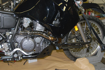 If your bike is fitted with the Happy Trails PD Nerf System remove the two outside upper bolts (5 mm hex) and nuts (10 mm) and rotate the guard out of the way.   HTP4-8-30  Odyssey Battery Kit Install www.happy-trail.com