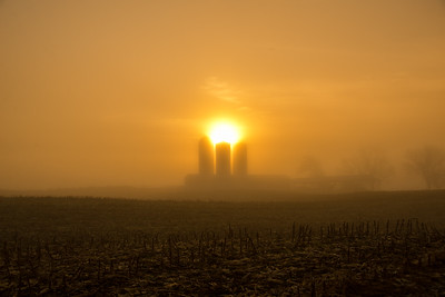 The three silos appear to be lifting the sun up through the fog.