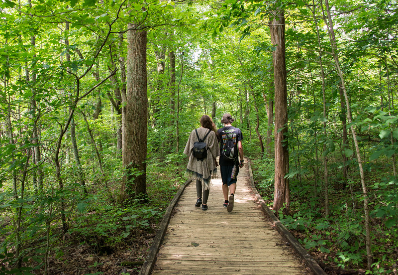 A young couple holding hands and walking the trail at Sloan's Crossing