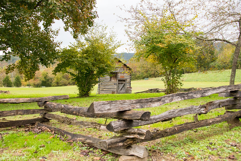 A small cabin nestled behind a split rail fence at the visitors center.