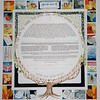 K 014 - Tree trunk holds circle which contains Ketubah text.  Judaic symbols as well as interests of couple make up border.  Pictures are more in the style of stained glass windows than realistic.
