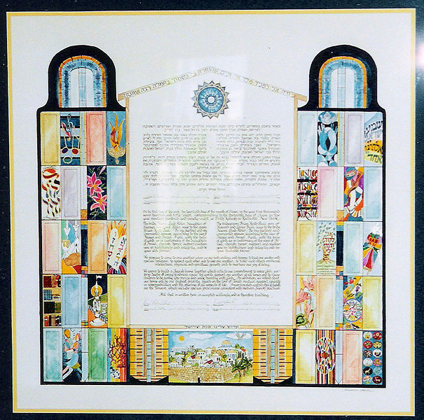 K 026 - Ketubah is done in a modern type of stained glass effect.  Over-all pattern symbolizes a torah scroll which surrounds a house.  Round stained glass window in center is a replica of one destroyed in bride's grandfather's synagogue in Germany on Kristallnacht. There are many Judaic symbols in the design including Jerusalem, Havdalah set, books etc. & interests of groom (a rabbi) and bride (a lawyer).
