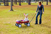 Kid girl and mother walking in park with pull cart