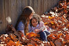 Kid girl friends playing tablet pc in autumn leaves