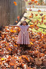Toddler kid girl playing with autumn leaves