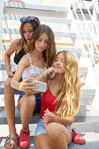 Teen best friends girls in a row with smartphone