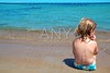 Little blond girl sit in beach shore looking ocean