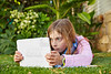 Blond kid girl with tablet pc lying on grass turf
