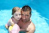 father daughter hug on blue swimming poo
