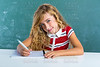 Blond student girl writing notebook at class desk