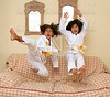 Two little asian judo gils jump on sofa