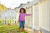 Toddler kid girl portrait in a park fence