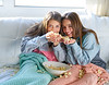 best friend girls at sofa having fun with popcorn