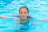 Blond girl swimming in the pool with red cheeks