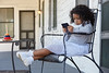 Kid girl sitting in the porch playing smartphone