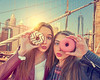 Teen girls portrait with donuts in eye New York