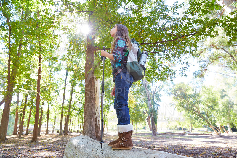 Hiker girl with hiking pole and backpack in forest full length