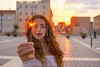 Teen girl with sparklers at sunset in the city