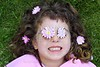 little girl laying grass daisiy flowers in eyes
