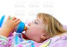girl drinking bottle of milk laying on bed