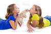 happy twin sister kid girls kissing puppy dog lying