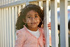 Happy toddler kid girl portrait in a park fence