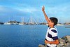 farewell boy rising hand up goodbye in boats marina