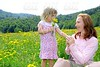 Daughter and mother playing in flowers meadow