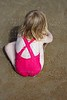blond little girl swimsuit back playing on beach sand