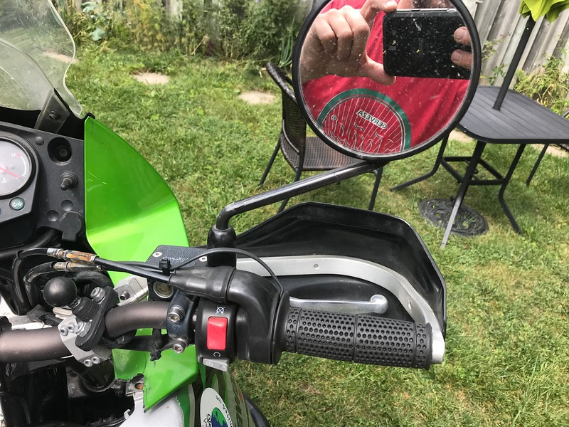 Note the broken plastic.  I had repaired it fairly well once but it broke again.  Not that the right mirror is replacement glass and not exactly the same as stock.  The Pro-Taper grips are heated by Symtech heating elements.