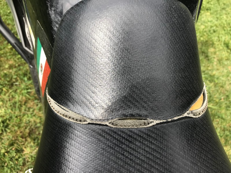 Probably can be repair by someone who works with leather.  Undo the rivets/stables, sew up and cover with fresh piece of leather, the re-staple.