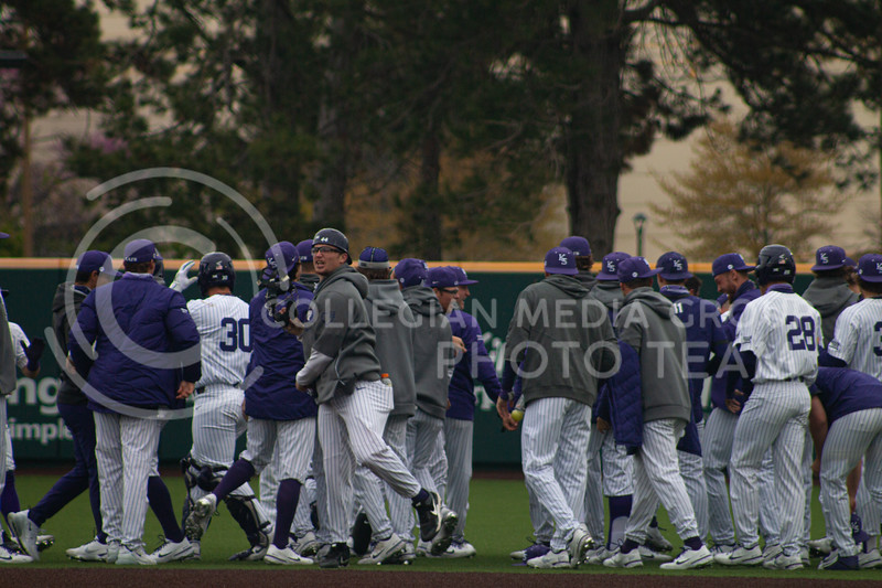 The Kansas State University baseball team cheers in a group huddle after rushing their home field. The team celebrates a 3-2 victory in the first game of their double header against Oklahoma University <br /> on Saturday, April 17th. (Natalie Leonard l Collegian Media Group)