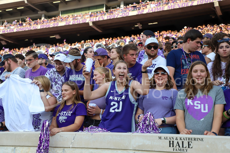 Students celebrating catching a t-shirt from the cheerleaders.