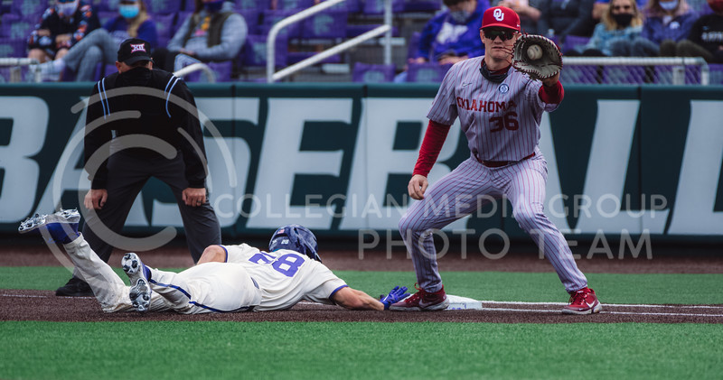 Wildcat's base runner, Zach Kokoska, dives for back to first base. Kokoska finished the evening with one R, two H, one RBI, and one BB against OU. Kansas State University baseball capped off the weekend by defeating Oklahoma 8-3 at Tointon Family Stadium, Manhattan KS. 4/18/21. (Dylan Connell | Collegian Media Group)