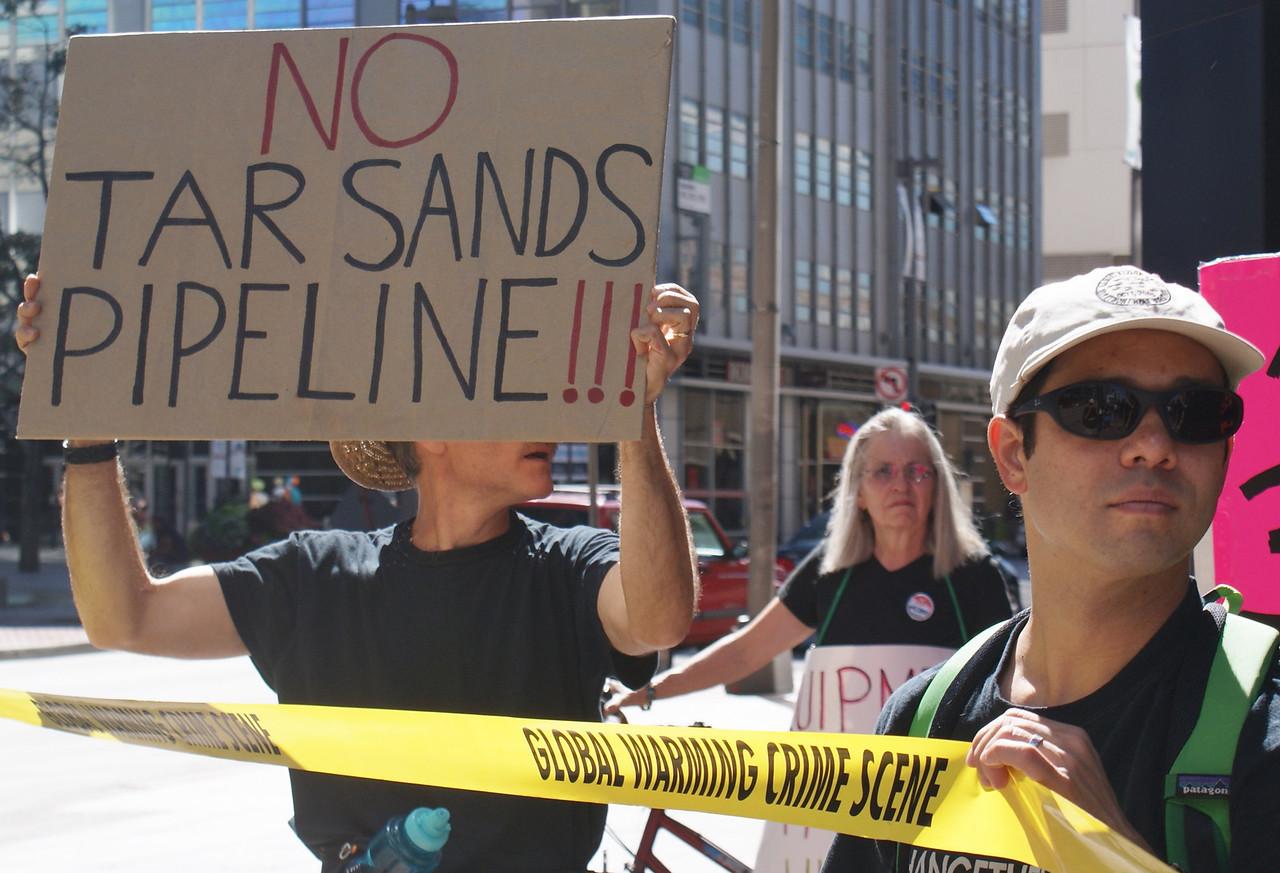 """Anti KXL pipeline protester holding """"global warming crime scene"""" tape."""