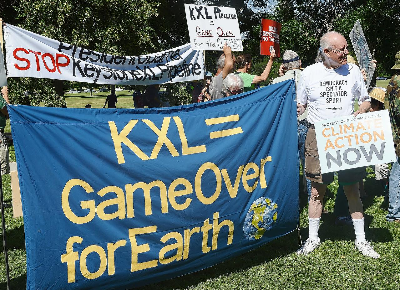 Senior man holding large banner  opposing KXL pipeline.