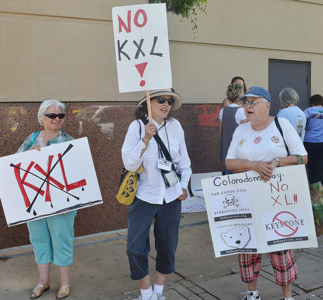 Three women at protest against KXL pipeline holding signs.