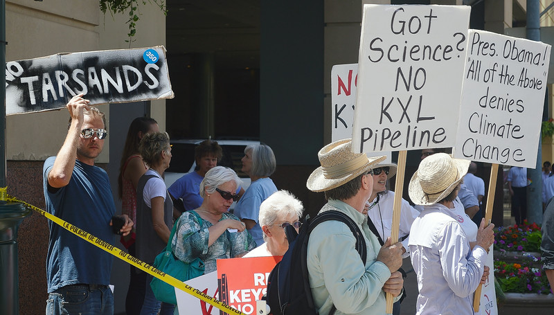 Group of anti KXL pipeline demonstrators hoding signs including one directed at President Obama.