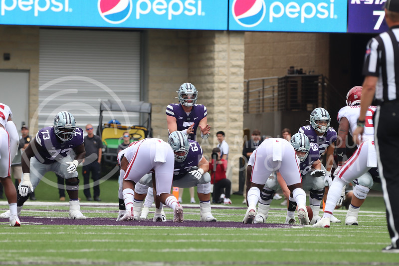 On an offensive drive, Senior Skylar Thompson waits to receive the snap from Senior Noah Johnson in the Oklahoma University game on October 2, 2021. <br /> (Macey Franko   Collegian Media Group)
