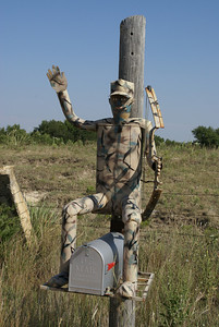 Camouflaged bow hunter on mailbox - Ellis County