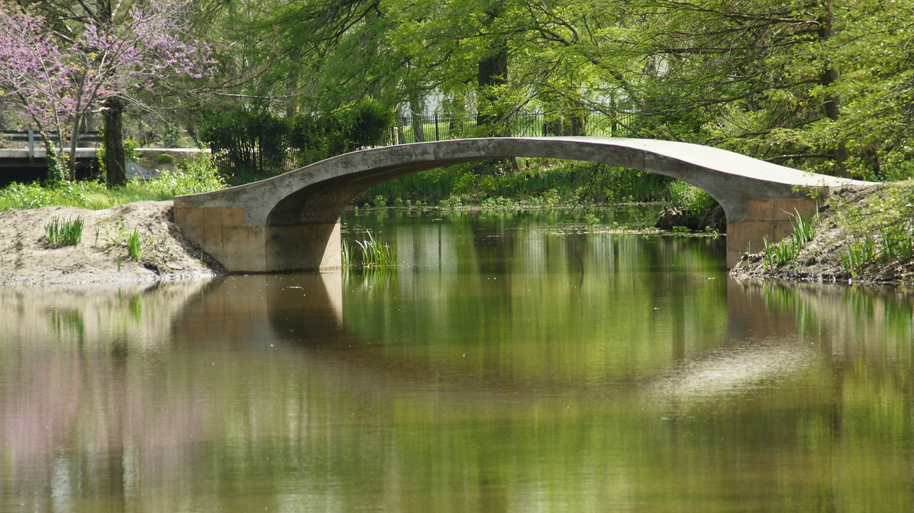 Arch bridge over pond with reflections in water. Photo by Larry.