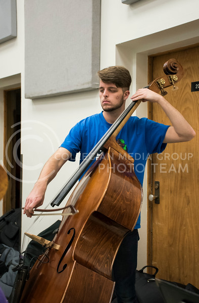 An upright bass player pays close attention to their music during rehearsal for the Kansas State Orhestra in the McCain Buidling in Manhattan, KS, on Nov. 6, 2017. (Olivia Bergmeier | Collegian Media Group)