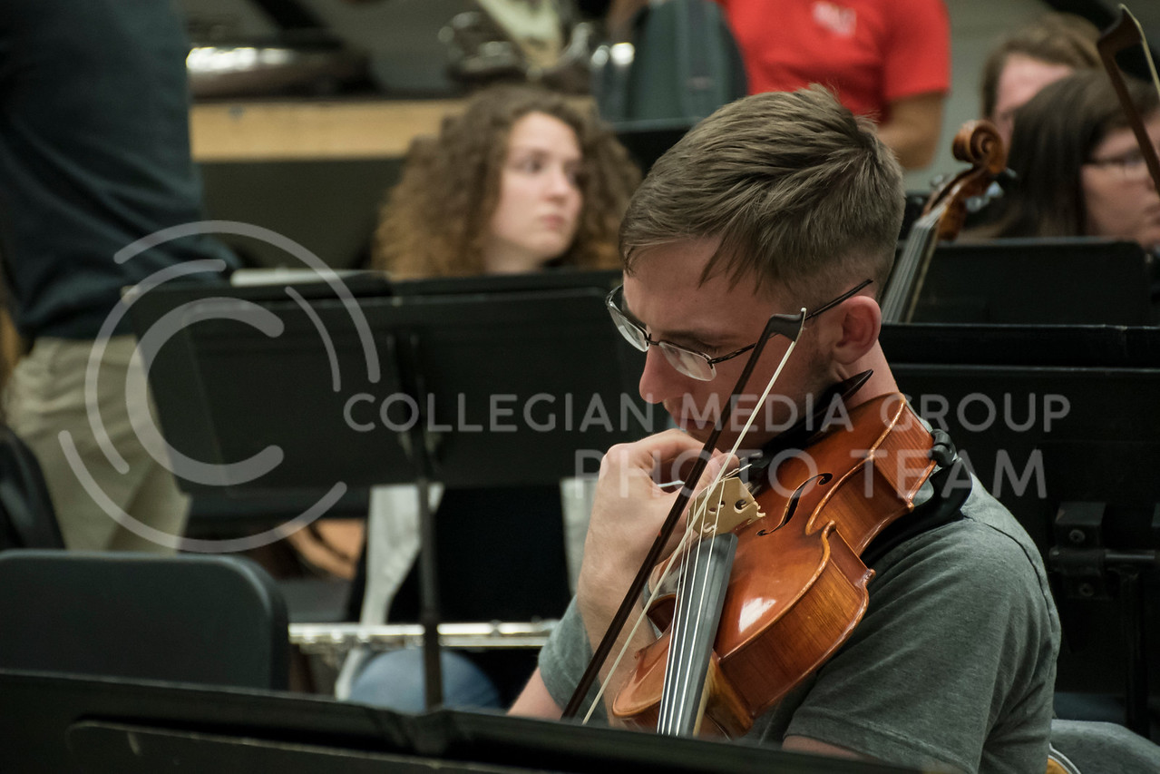 A student makes sure that their instrument is in perfect tune in the Kansas State Orchestra Rehearsal in the McCain Buidling, in Manhattan, KS, on Nov. 6, 2017. (Olivia Bergmeier | Collegian Media Group)