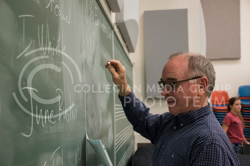 Dr. Litrell writes the rehearsal schedule for the Kansas State Orchestra on the chalk board in the McCain Building in Manhattan, KS, on Nov. 6, 2017. (Olivia Bergmeier | Collegian Media Group)