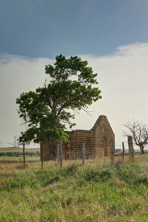 An old farm house long forgotten and abandoned sit alone on the prairie.