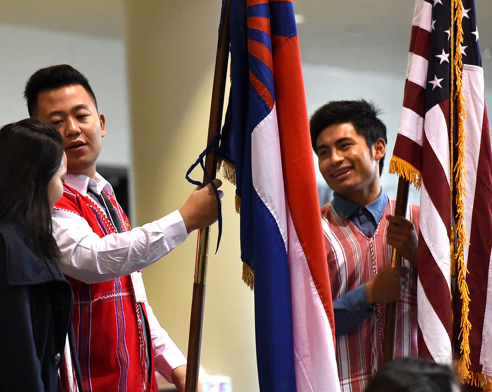 . Poe Eh Day, left, talks to a friend before he and Tar Baw carry the Karen and American flags down to the front at the beginning of a Karen New Year Celebration at Washington Technology Magnet School in St. Paul on Friday, January 1, 2016. (Pioneer Press: Jean Pieri)