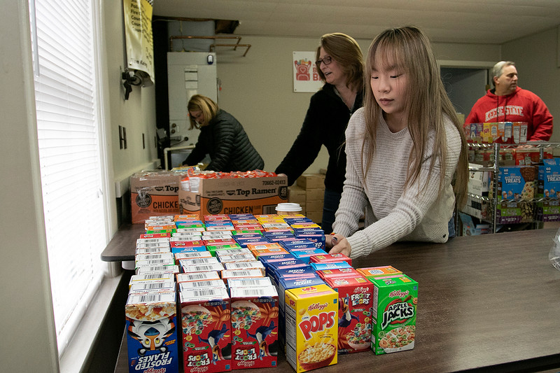 Karing 4 Kidz in Fitchburg, started by Kira Andreucci at the age of 10 now 19, was still putting together lunches for the students in the district on Wednesday night, March 25, 2020 with her mom and dad and some volunteers. In the lunches was a Rice Crispy Treat, a fruit snack, granola bar apple sauce, cereal, two Caprisun Juices, Ramen Noodles, a can of Chef Boyardee, and some oatmeal. They package 250 meals each week for the students in need. Kira gets ready to start packaging the meals. SENTINEL & ENTERPRISE/JOHN LOVE