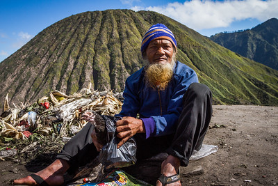 At the summit of Mt Bromo a Tengger man prepares his offering of a chicken before throwing it into the volcano.